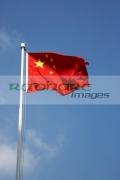 chinese-flag-flying-against-blue-sky-on-flagpole