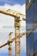 yellow-cranes-against-blue-cloudy-sky-working-on-construction-site-near-plate-glass-building-in-Belfast-City-Centre