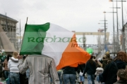 Family-carry-Irish-tricolour-towards-harland-wolff-shipyard-cranes,-symbol-unionism-during-St-Patricks-Day-Parade,-at-St-Patricks-Day-Celebrations,-Belfast-City-Centre.