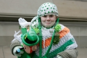 Young-girl-awaits-the-St-Patricks-Day-Parade,-at-St-Patricks-Day-Celebrations,-Belfast-City-Centre.