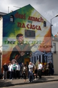 people-gather-on-beechmount-avenue-beneath-the-easter-rising-mural-on-easter-sunday-to-commemorate-the-easter-rising-on-the-falls-road-belfast