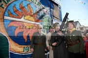 reinactors-dressed-as-an-old-IRA-flying-column-stand-in-front-the-Fianna-Eireann-mural-on-Easter-Sunday-at-the-Easter-Rising-Commemoration-Falls-Road-Belfast-Northern-Ireland-UK