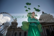 stiltwalker-dressed-in-green-wearing-shamrocks-at-belfast-city-hall-big-wheel-before-the-parade-carnival-on-st-patricks-day-belfast-northern-ireland