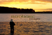 fisherman-fly-fishing-on-Stoneyford-Reservoir-at-sunset,-county-antrim-northern-ireland