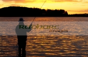 fisherman-fly-fishing-casting-on-Stoneyford-Reservoir-at-sunset,-county-antrim-northern-ireland
