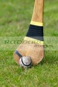 used-leather-sliothar-hurling-ball-beside-head-caman-hurley-stick-on-grass