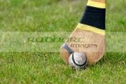 used-leather-sliothar-hurling-ball-beside-head-taped-caman-hurley-stick-on-grass