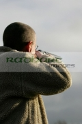 man-with-glasses-in-fleece-jacket-aiming-shotgun-into-sky-on-december-shooting-day,-county-antrim,-Northern-Ireland