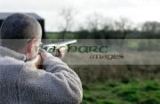 man-with-glasses-in-fleece-jacket-firing-shotgun-into-field-on-december-shooting-day,-county-antrim,-Northern-Ireland