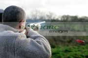 man-in-fleece-jacket-firing-shotgun-into-field-with-cartridge-ejecting-on-december-shooting-day,-county-antrim,-Northern-Ireland
