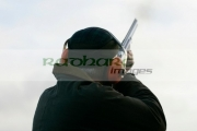 man-in-cap-orange-ear-defenders-takes-aim-into-sky-with-shotgun-on-december-shooting-day,-county-antrim,-Northern-Ireland