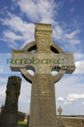 high-stone-celtic-cross-against-blue-cloudy-sky-in-the-Rock-Cashel,-Cashel,-County-Tipperary,-Republic-Ireland
