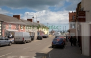 cars-parked-tourists-walking-up-down-main-street-courtown-traditional-seaside-resort-village