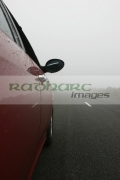 red-alfa-romeo-156-car-heading-along-country-mountain-road-shrouded-in-fog-mist-IOM