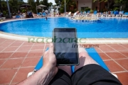 man-reading-ebook-on-tablet-computer-by-the-side-swimming-pool-on-holiday-salou-costa-daurada-spain